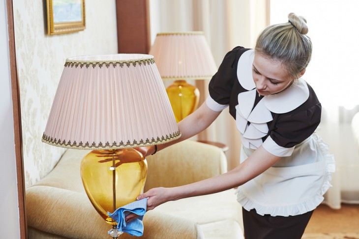 Hotel service. female housekeeping worker with cleaning table fr