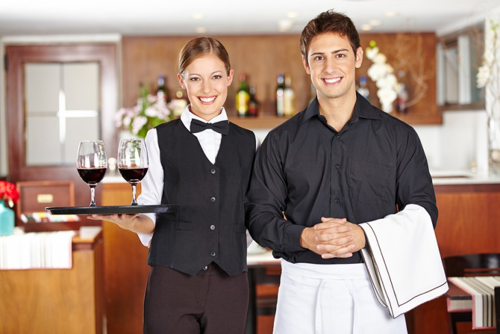 Team of waiter staff with wine glasses in a restaurant