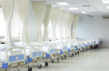 Rows of hospital beds with linens that require laundering and care